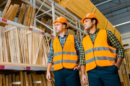 Photo for Multicultural warehouse workers in safety vasts and helmets standing near racks with wooden construction materials - Royalty Free Image