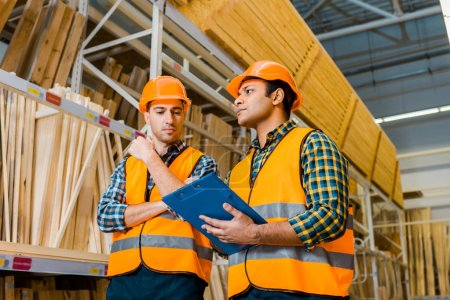 Photo for Concentrated multicultural workers with clipboard standing near racks with wooden construction materials - Royalty Free Image