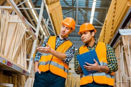 Photo pour Beau travailleur multiculturel pointant à la main les matériaux de construction en bois près d'un collègue indien - image libre de droit