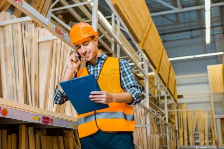 smiling warehouse worker talking on smartphone and looking at clipboard