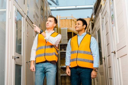 Photo for Handsome warehouse worker pointing with finger at doors near smiling indian coworker - Royalty Free Image