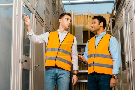 Photo for Multicultural warehouse workers talking while standing in doors department - Royalty Free Image