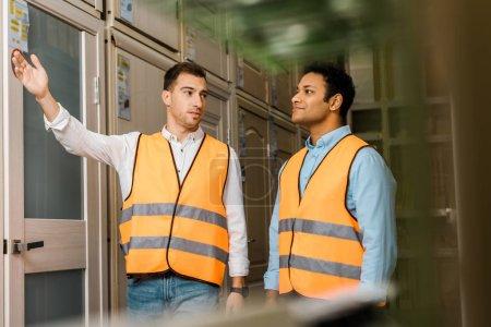 Foto de Enfoque selectivo de los trabajadores multiculturales que hablan mientras están de pie en el Departamento de puertas - Imagen libre de derechos