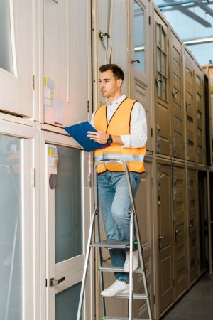 Photo for Handsome, serious warehouse worker with clipboard standing on ladder in doors department - Royalty Free Image
