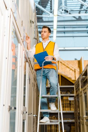 Photo for Selective focus of concentrated worker in safety vest standing on ladder in doors department - Royalty Free Image