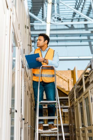 Photo for Selective focus of attentive indian worker in safety vest standing on ladder in warehouse - Royalty Free Image