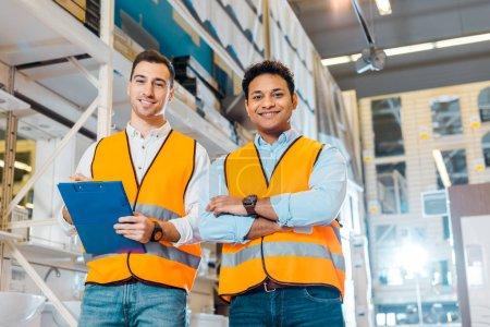 Photo pour Souriant ouvriers d'entrepôt multiculturelle souriant et regardant l'appareil-photo - image libre de droit