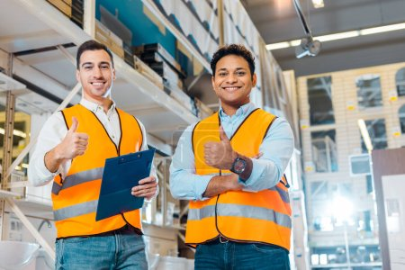 cheerful multicultural warehouse workers showing thumbs up and looking at camera