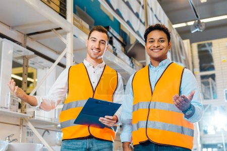 Photo pour Souriant travailleurs multiculturels entrepôt dans des gilets de sécurité souriant et regardant la caméra - image libre de droit