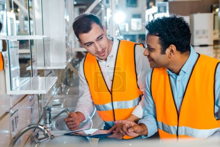Photo for Smiling multicultural colleagues in safety vests working in plumbing department - Royalty Free Image