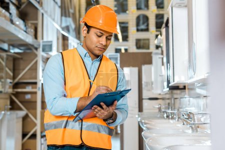 Photo for Selective focus of serious indian worker writing in clipboard in plumbing department - Royalty Free Image