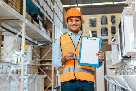 Photo for Smiling indian warehouse worker showing clipboard with blank paper and looking at camera - Royalty Free Image