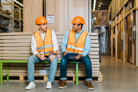 Photo for Smiling multicultural workers in safety vests and helmets resting on bench in warehouse - Royalty Free Image