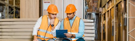 Photo for Panoramic shot of serious multicultural workers sitting on bench in warehouse and looking at clipboard - Royalty Free Image