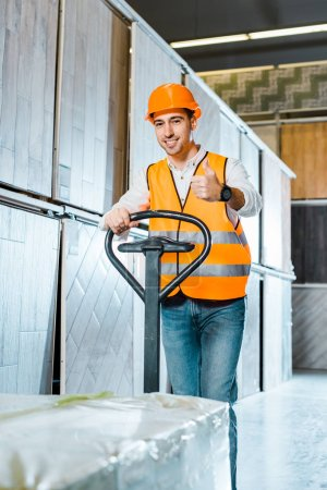 Photo for Smiling worker carrying pallet jack and showing thumb up - Royalty Free Image