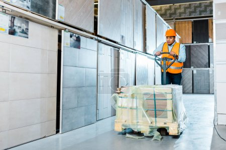 Photo for Serious indian warehouse worker carrying pallet jack in tiles department - Royalty Free Image