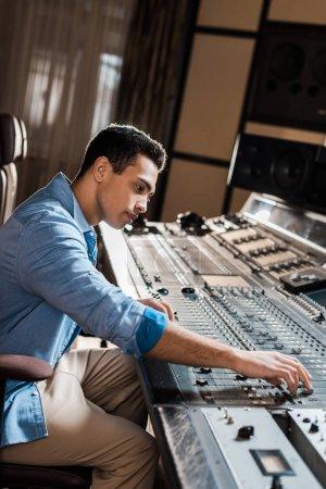 Photo pour Beau producteur de son de course mixte travaillant à la console de mixage dans le studio d'enregistrement - image libre de droit