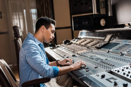 Photo for Attentive mixed race sound producer working at mixing console in recording studio - Royalty Free Image