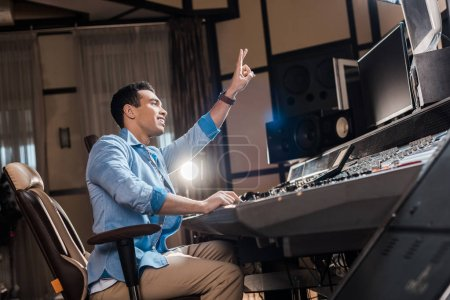 Photo pour Handsome mixed race sound producer showing victory sign while working in recording studio - image libre de droit