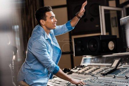 Photo pour Mise au point sélective de sourire mixte de race producteur sonore gestuelle tout en travaillant dans le studio d'enregistrement - image libre de droit