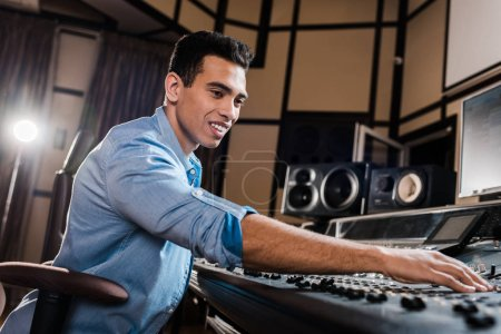 Photo pour Producteur de son de course mélangé de sourire travaillant à la console de mélange dans le studio d'enregistrement - image libre de droit
