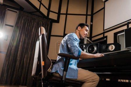 Photo pour Beau producteur de son de course mixte travaillant dans le studio d'enregistrement à la console de mixage - image libre de droit