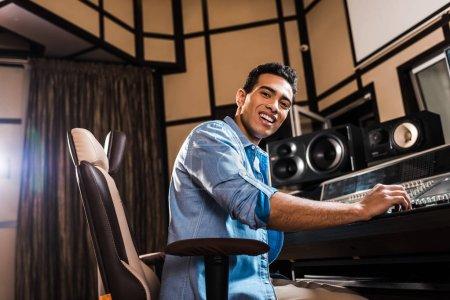 Photo pour Joyeux producteur de sons métis assis dans une chaise de bureau dans un studio d'enregistrement et regardant la caméra - image libre de droit