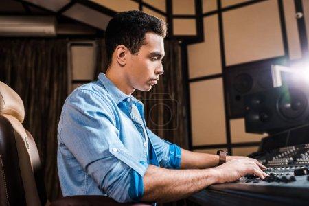 Photo pour Producteur sonore métissé concentré travaillant à la console de mixage en studio d'enregistrement - image libre de droit
