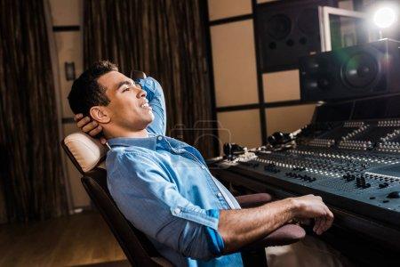 Photo pour Producteur de son de course mélangé de sourire détendant dans la présidence de bureau dans le studio d'enregistrement - image libre de droit
