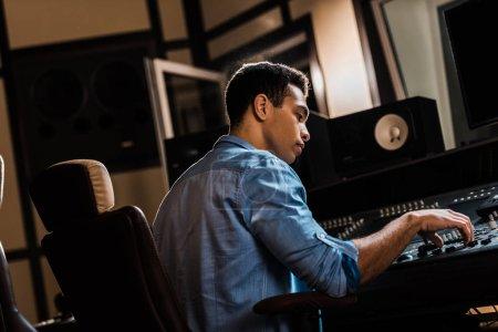 Photo pour Sérieux producteur de son de race mixte travaillant à la console de mixage en studio d'enregistrement - image libre de droit