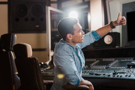 Photo pour Producteur de son de course mélangé de sourire affichant le pouce vers le haut tout en travaillant dans le studio d'enregistrement - image libre de droit
