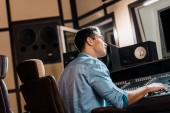 "Постер, картина, фотообои ""attentive mixed race sound producer working at mixing console in recording studio"""
