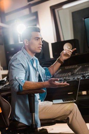 Photo pour Sérieux mix race producteur sonore gestuelle tout en étant assis à la console de mixage dans le studio d'enregistrement - image libre de droit