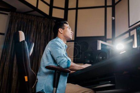 Photo pour Beau producteur de son de race mixte travaillant dans le studio d'enregistrement - image libre de droit