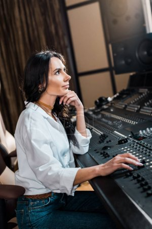 Photo for Beautiful sound producer working on mixer console in recording studio - Royalty Free Image