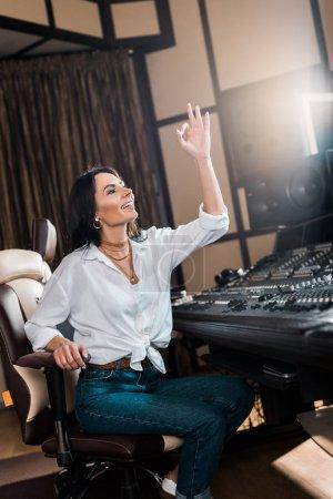Photo pour Producteur sonore attrayant affichant le signe ok et souriant dans le studio d'enregistrement - image libre de droit