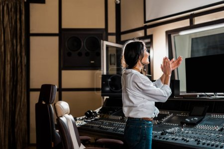 Photo for Attractive sound producer applauding in recording studio near mixing console - Royalty Free Image