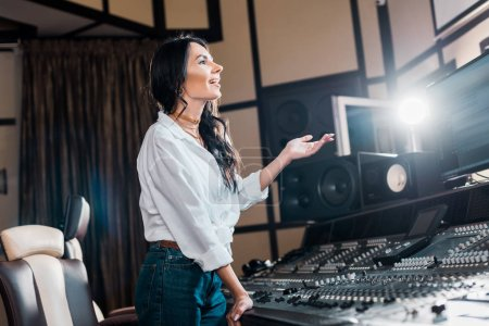 Photo for Happy sound producer applauding in recording studio near mixing console - Royalty Free Image