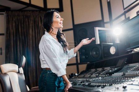 Photo pour Producteur de son heureux applaudir dans le studio d'enregistrement près de la console de mixage - image libre de droit