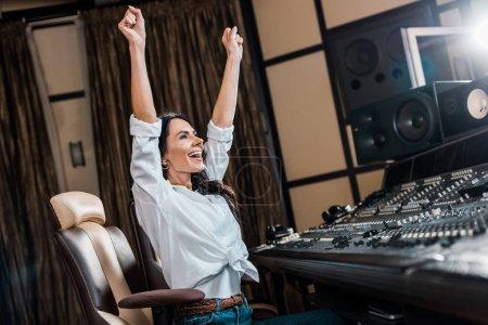 Photo pour Producteur de son heureux montrant le geste de succès près de la console de mixage dans le studio d'enregistrement - image libre de droit