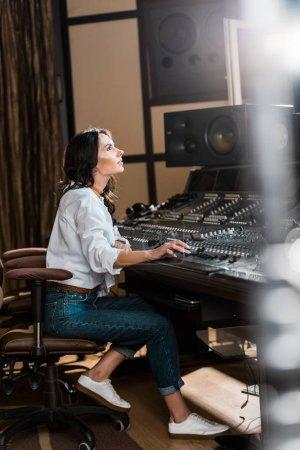 Photo pour Mise au point sélective de producteur sonore attrayant travaillant à la console de mixage en studio d'enregistrement - image libre de droit