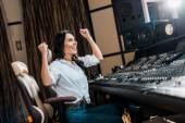"""Постер, картина, фотообои """"веселый звукорежиссер, показывающий жест победителя, сидя возле микшерной консоли в студии звукозаписи"""""""