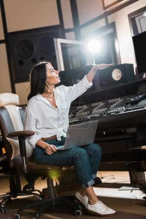 Photo for Attractive sound producer gesturing while working in recording studio - Royalty Free Image