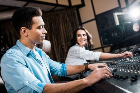 Photo for Selective focus of good-looking mixed race sound producer working at mixing console near pretty smiling colleague - Royalty Free Image