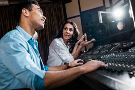 Photo for Selective focus of pretty sound producer gesturing near mixed raced colleague working at mixing console - Royalty Free Image
