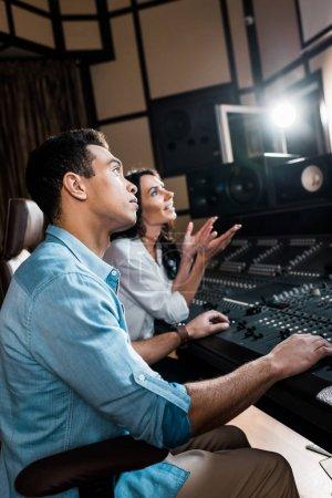 Photo pour Mise au point sélective des producteurs sonores travaillant à la console de mixage en studio d'enregistrement - image libre de droit
