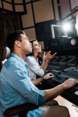 "Постер, картина, фотообои ""selective focus of sound producers working at mixing console in recording studio"""