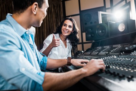 Photo for Selective focus of pretty sound producer showing thumb up near handsome mixed race colleague working at mixing console - Royalty Free Image
