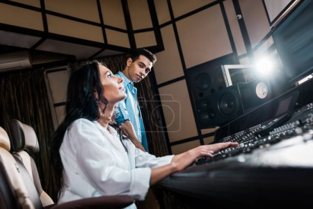 Photo for Young multicultural sound producers working at sound console in recording studio - Royalty Free Image
