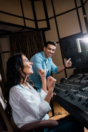 Photo for Two happy multicultural sound producers showing success gestures in recording studio - Royalty Free Image
